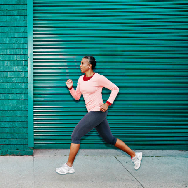 Athletic mature African American woman running.