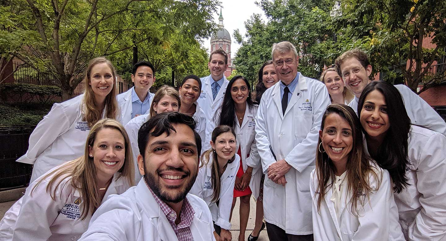Fellows in white lab coats outside of JHU dome smiling in a selfie.