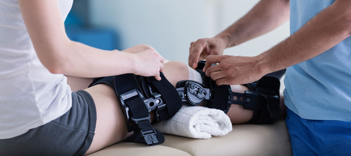 Doctor helping patient with knee brace