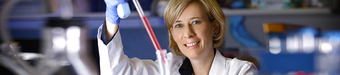 Doctor Charlotte Sumner using a pipette in the lab.