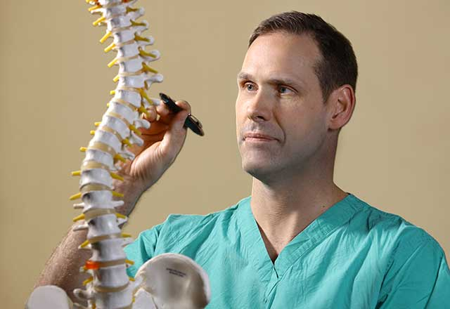 Dr. Witham with a model of the spine