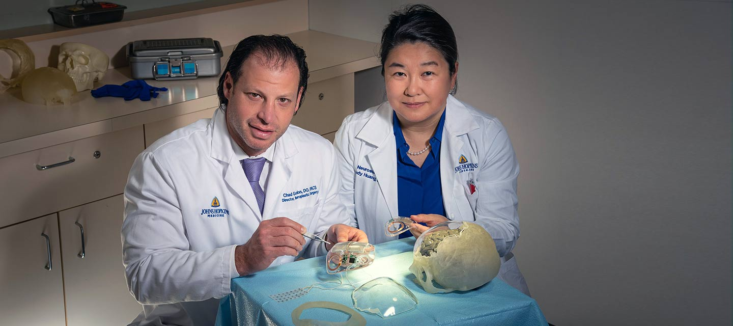 Drs. Gordon and Huang work with a skull implant device.