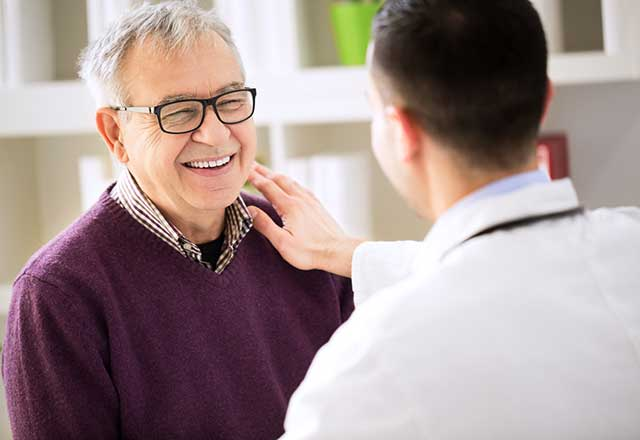 Younger doctor speaking with an older male patient