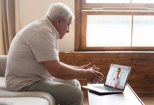 Elderly man video conferencing with physician