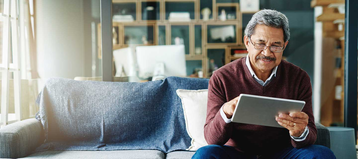 Older man looking at his tablet sitting on a couch.