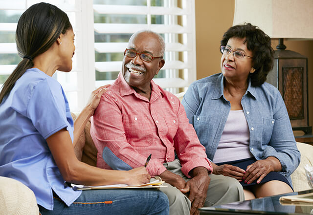 Healthcare provider talking to older woman and daughter.