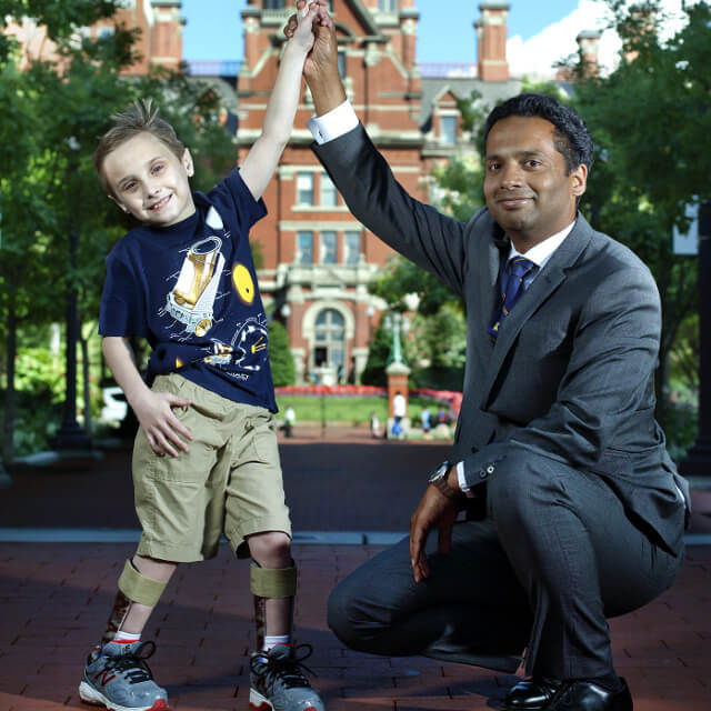 Dr. Varghese high-fiving a young patient