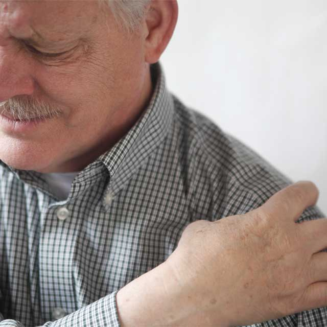 a man holds his shoulder while wincing in pain