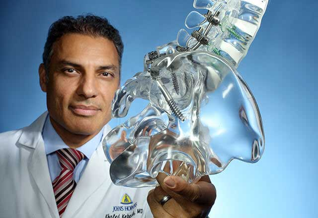 Dr Kebaish Khaled holding a model of a hip
