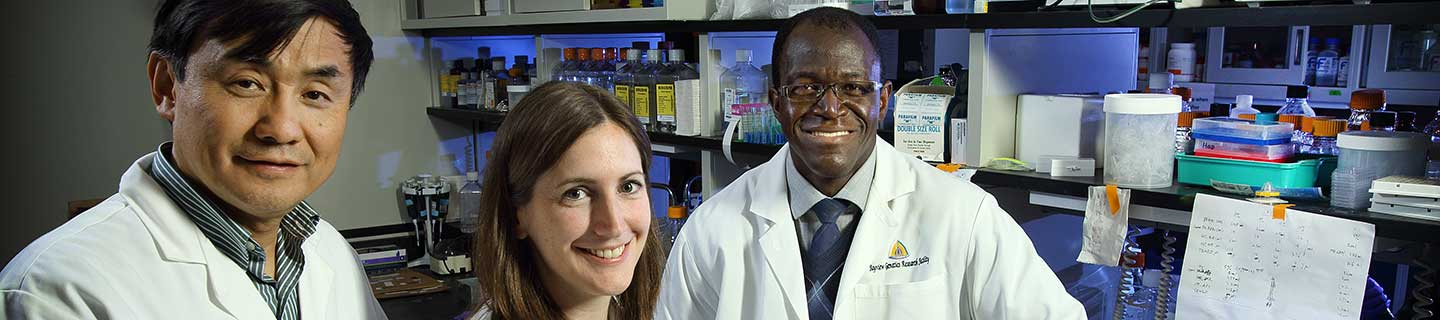 Researchers in a lab smiling.