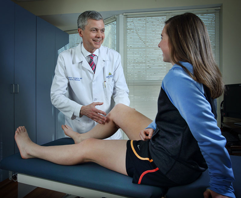 Dr. Andrew Cosgarea talks to a patient with an ACL injury