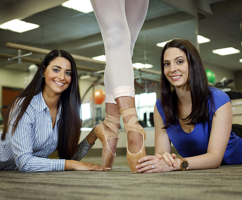 two physical therapists pose with a ballet dancer