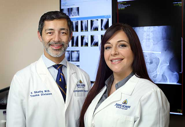 Dr. Shafiq and Practitioner Andra Love in front of x-rays
