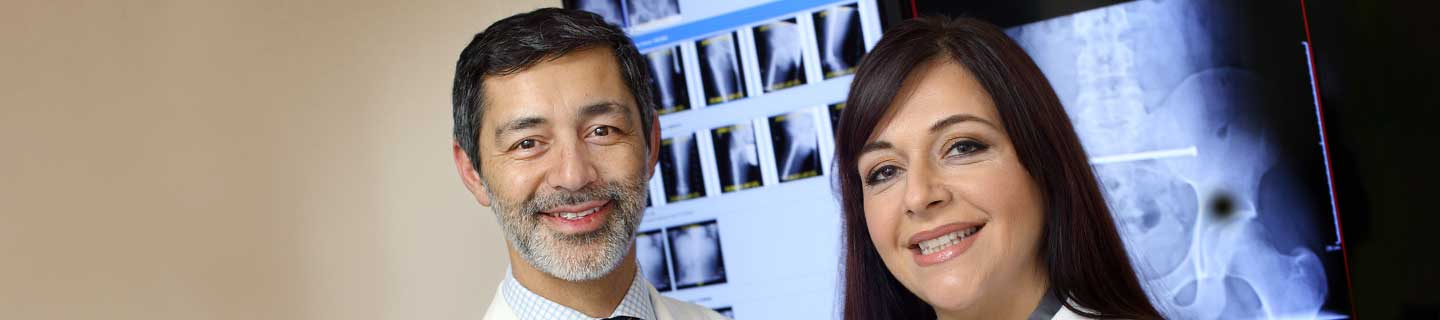 Dr. Shafiq and Andra Love standing in front of x-rays.