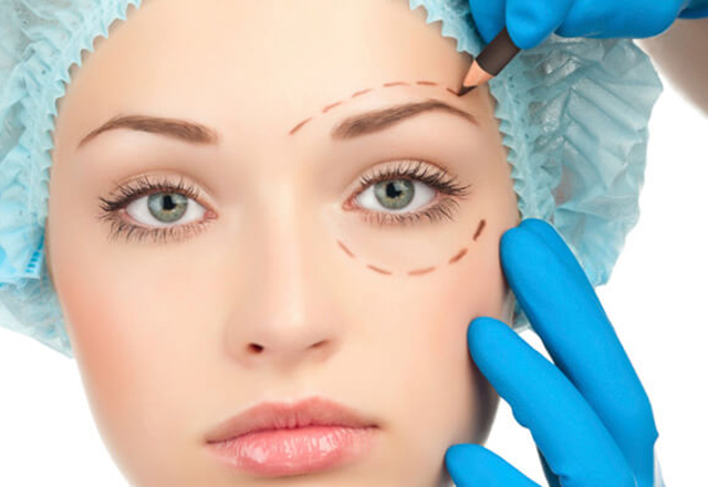 woman getting checked by facial plastic surgeon
