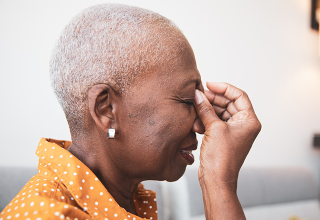 older woman holding nose