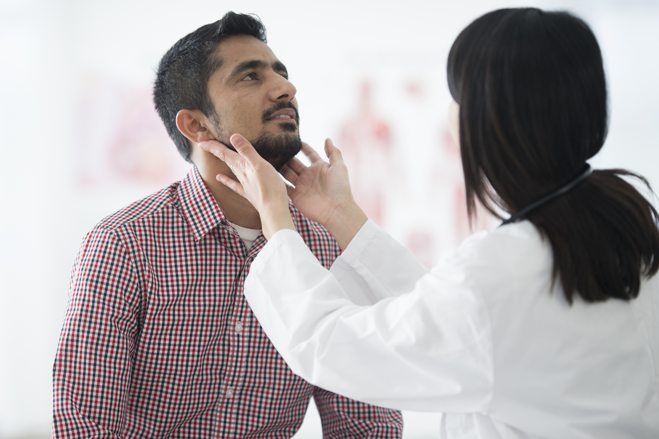 man getting his throat checked by doctor