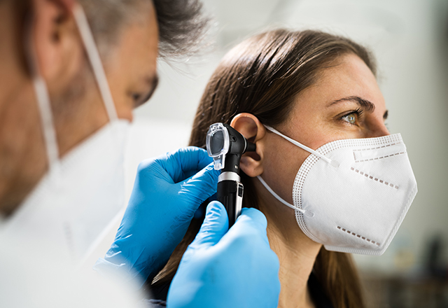 female patient's ear examined by doctor