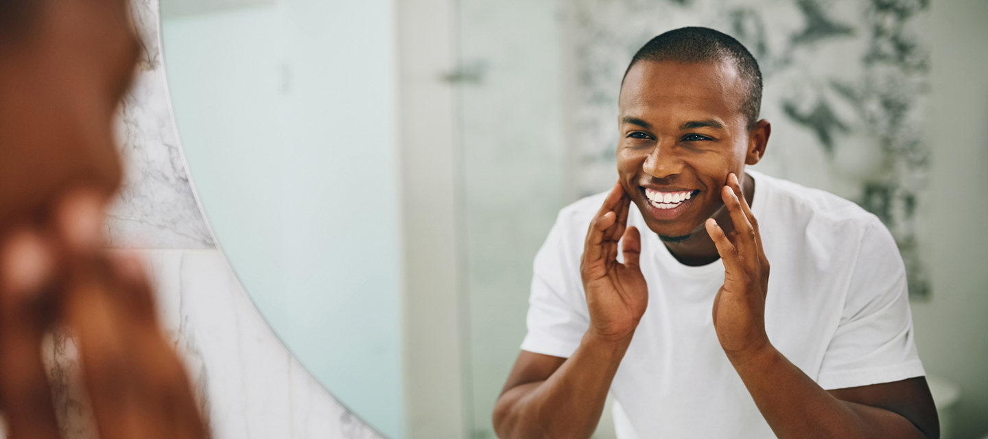 man smiling in front of mirror