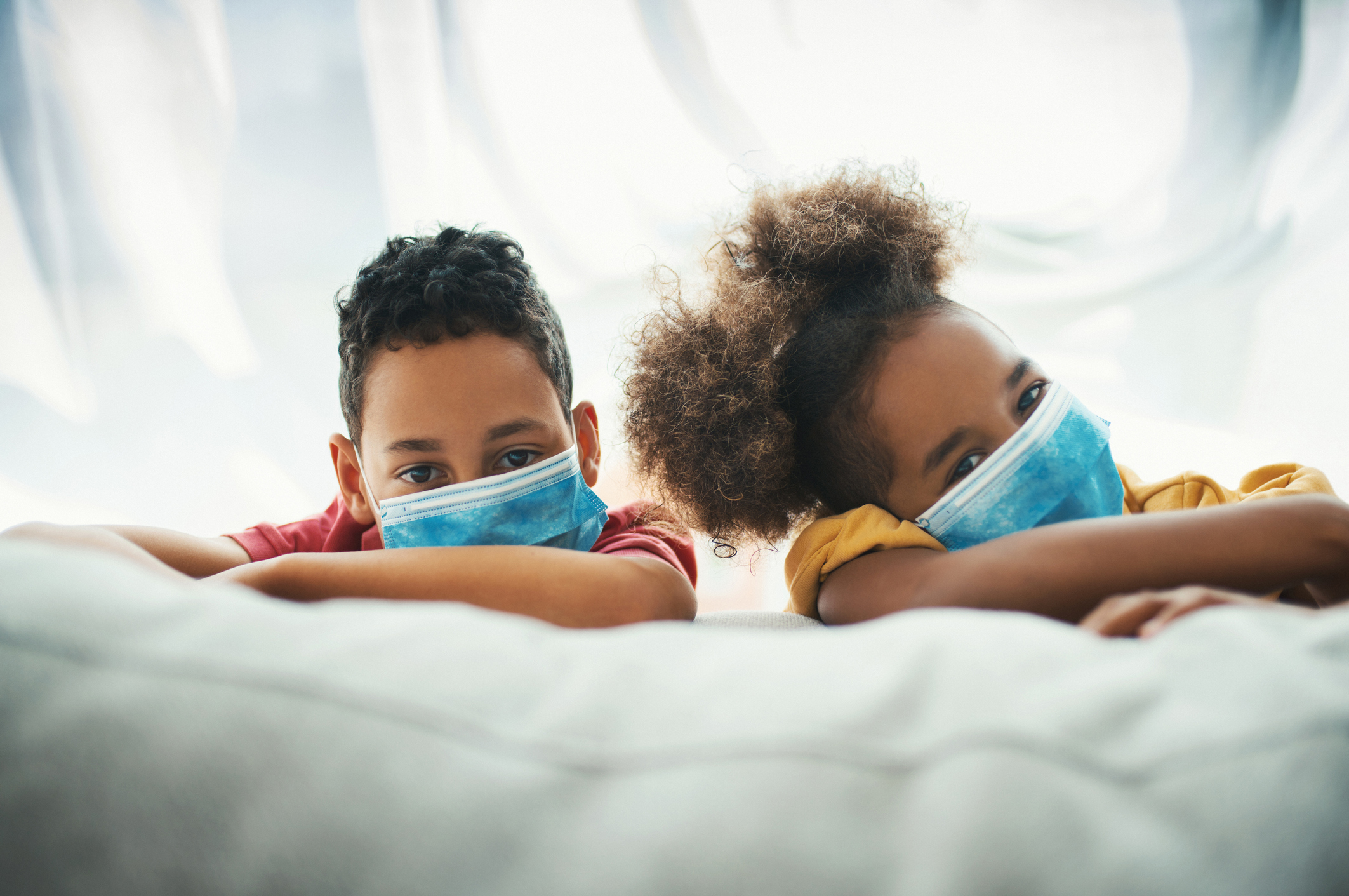kids wearing a mask on a couch