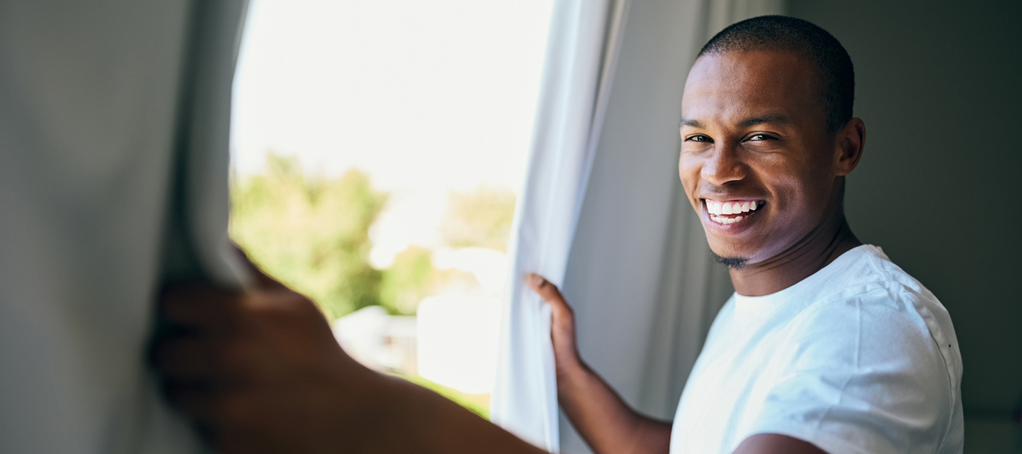 a man smiling next to a window
