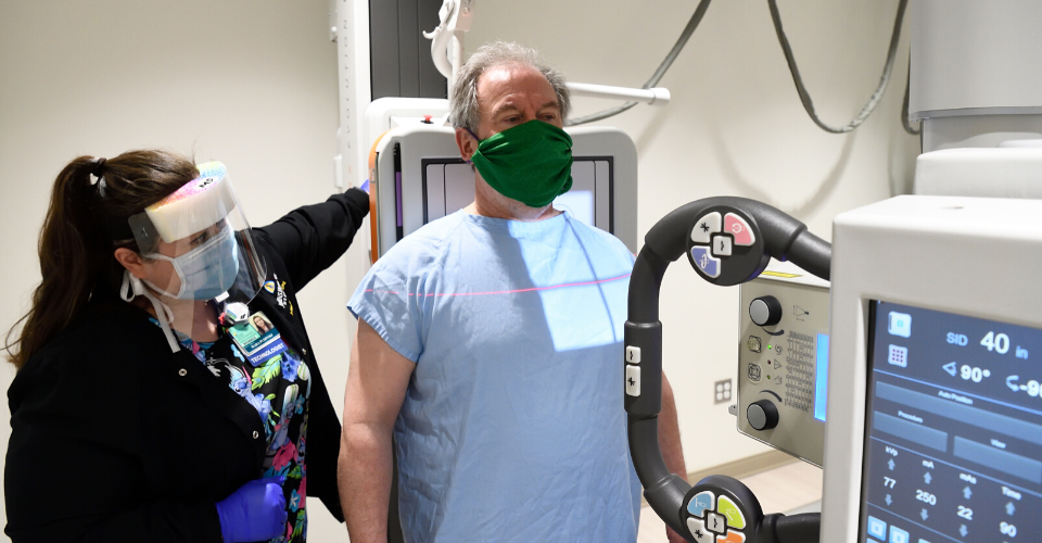 technologist performing chest x-ray on patient. Both are wearing masks