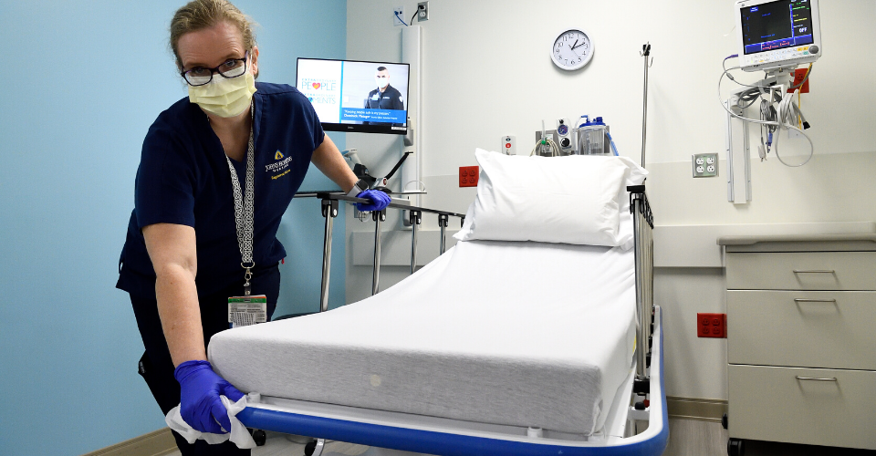 woman wearing a mask cleaning hospital bed