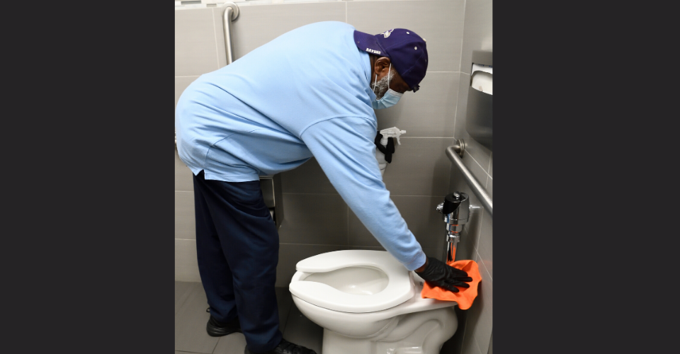 man wearing a mask cleaning a bathroom