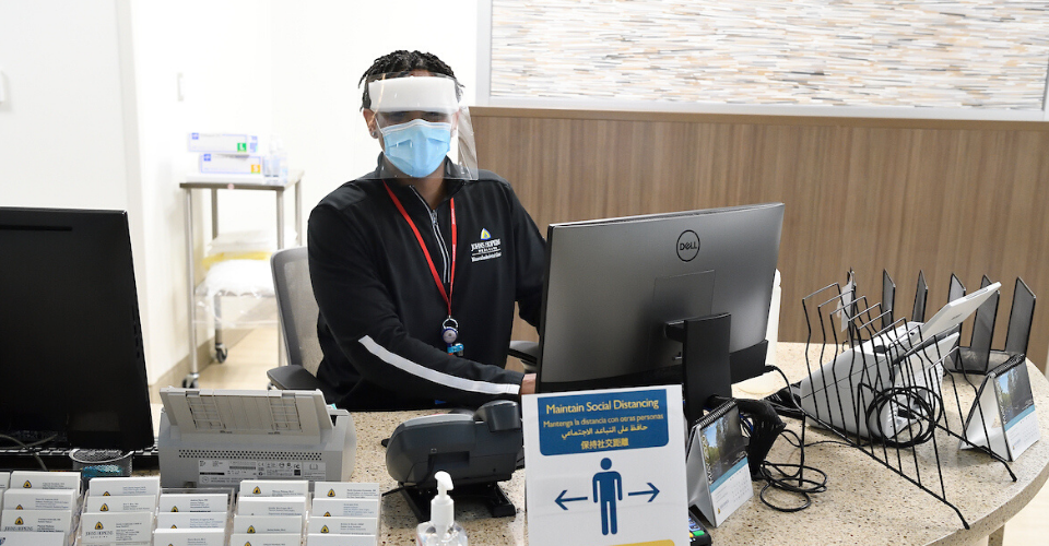 receptionist wearing a mask and face shield