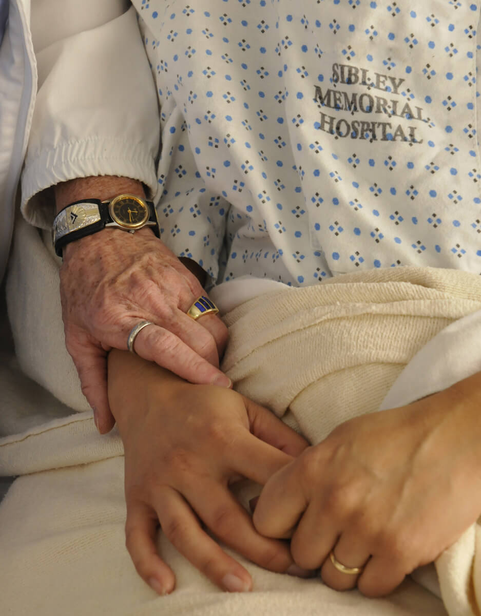 closeup of a chaplain holding a patient's hand