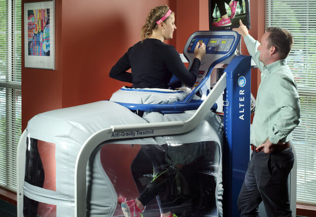 Physical therapists working with patient on anti-gravity treadmill.