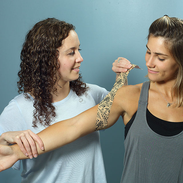 Therapist applying athletic tape to a patient's arm.