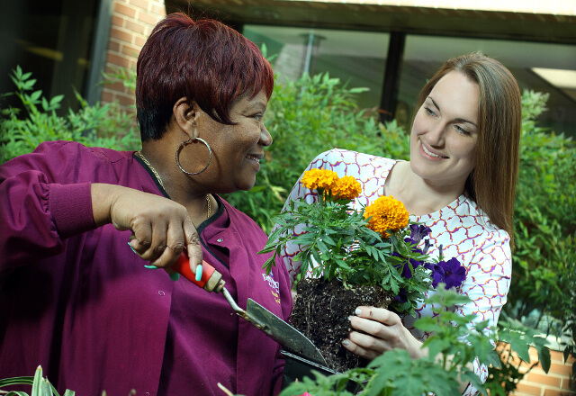 Mental health professional assisting client in a garden.