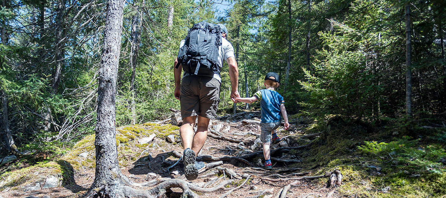 A father and son hike uphill while holding hands