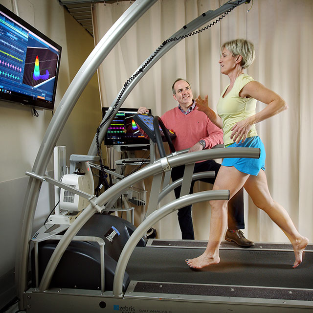 Therapist talking to a patient on a instrumented treadmill