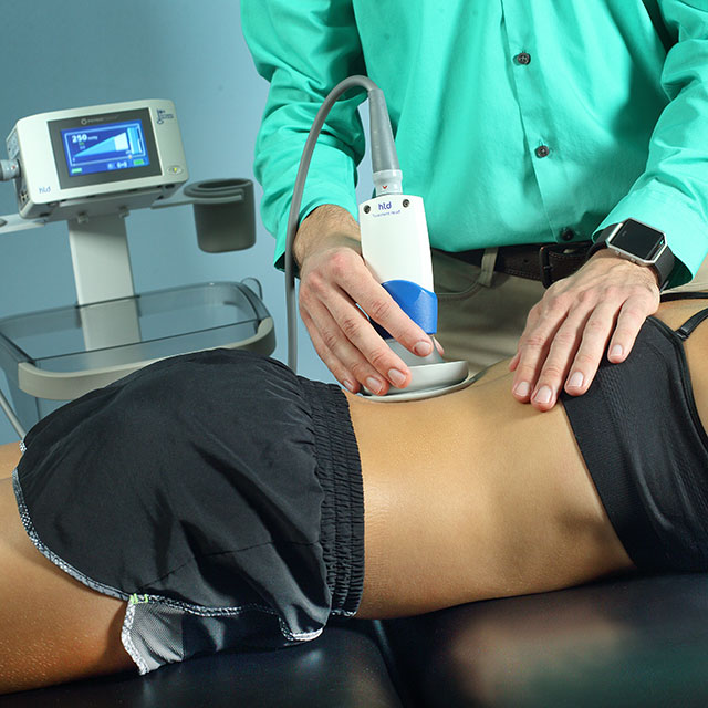 Therapist using a negative pressure machine on a patient's back.