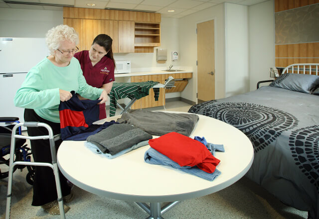 Nurse helping a patient with folding clothes.