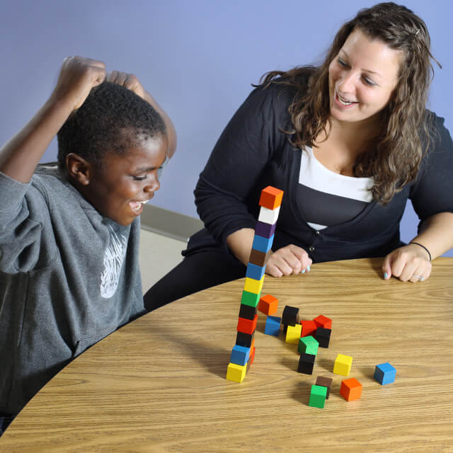 A boy working with an occupational therapist at the table