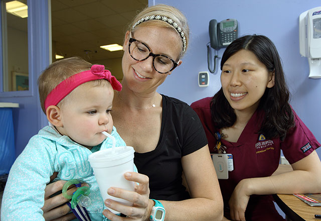 a speech-language pathologist works with a baby and her mother on swallowing