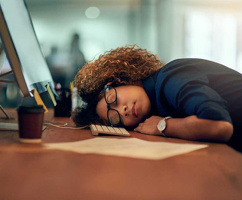 Tired woman asleep at her desk