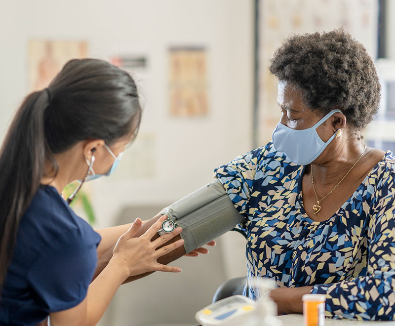 a masked nurse takes a masked patient's blood pressure