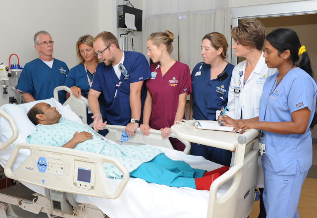 A clinical team gathered around a patient who had tracheostomy