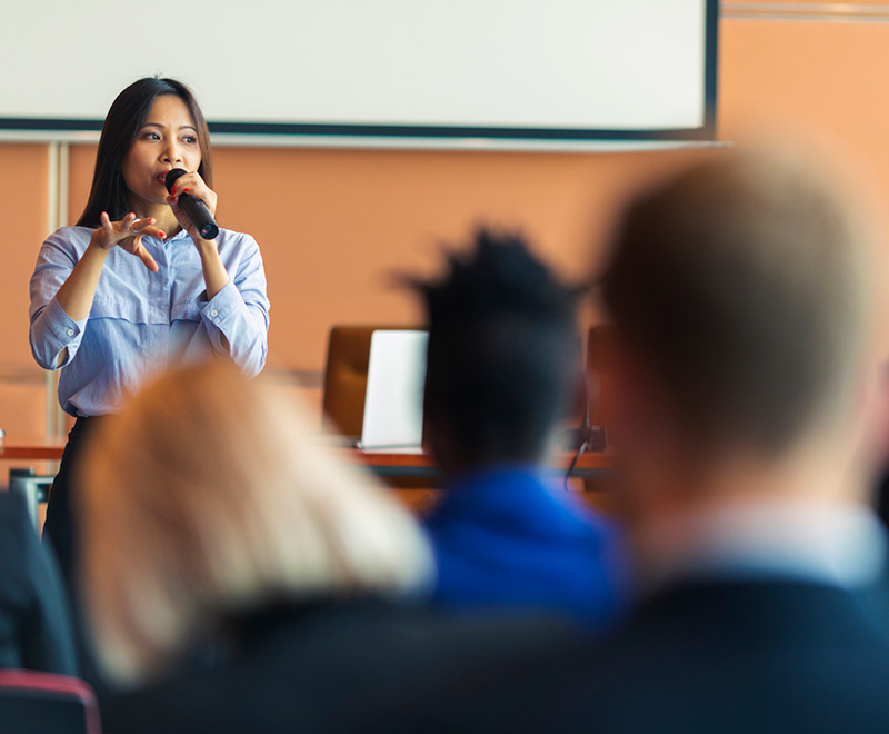 a woman speaks at a conference
