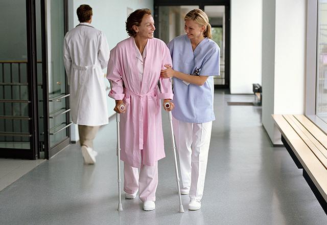 a clinician helping a patient walk