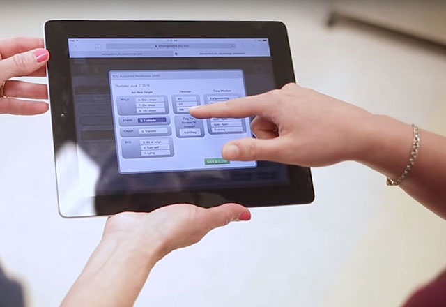 A nurse helping another track mobility on an iPad