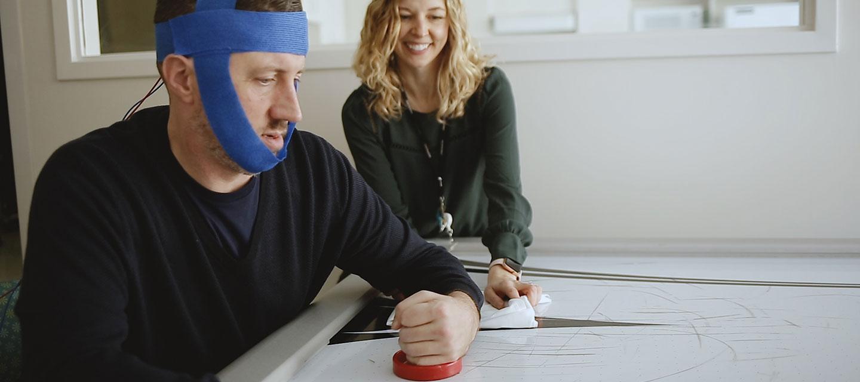 Two clinicians adjust noninvasive brain stimulation equipment on a male patient&#x27&#x3b;s head