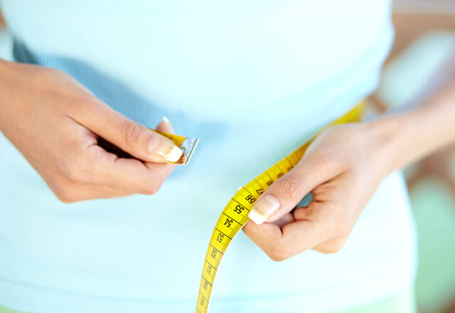 Measuring waist with tape