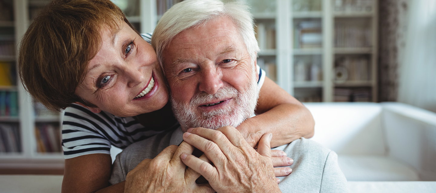 A senior couple share a happy embrace at home.