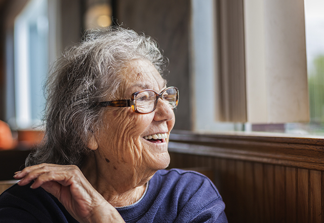 Happy senior woman looking out window