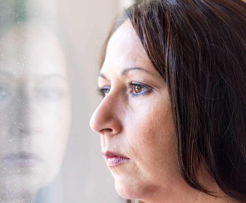 A woman looks out the window with a worried expression.